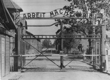 "The entrance to the main gate at Auschwitz I.  It reads ""work makes you free"".  Image courtesy of USHMM Photo Archives via http://fcit.usf.edu/holocaust"